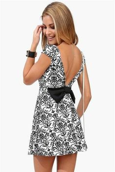 "Short black and white dress with black bow in back and large ""V"" cut."