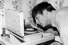 DJ John on the decks! Lennon's listening to a pre-release test pressing of the 'Twist And Shout' EP on a portable record player that travelled with the group on tour here. Not sure why the record player is rested on a sink, but hey.