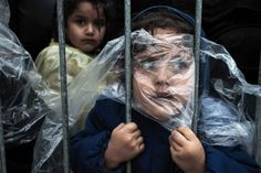 People, 1st prize singles. A child is covered with a raincoat while she waits in line to register at a refugee camp in Preševo, Serbia, Oct. 7, 2015.