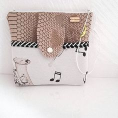 Trousse ou pochette main en simili cuir dragon marron taupe et tissu beige imprimé notes et instruments de musique avec grande poche sur le devant.