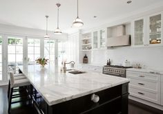 Porchlight Interiors    Black painted central kitchen island contrasting with white cabinetry and carrara marble counterops.