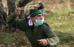 """soldiers-of-war: """"PALESTINIAN TERRITORIES. West Bank. Bilin. December 2010. A Palestinian protester uses a sling to throw stones at Israeli security forces during clashes at a protest against the controversial Israeli barrier in the village of Bilin..."""