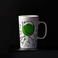A ceramic coffee mug featuring sketches of dogs drawn to a giant green ball. Part of the Dot Collection.