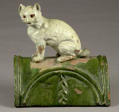 """French Figural Majolica Glazed Roof Tile, roof crest tile with seated white cat atop a green glazed base, impressed with markers cipher and Made In France; 12.75"""" long x 10"""" wide at bottom x 13.25"""" high."""