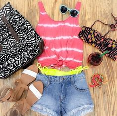 Tye-dye shirt with denim shorts and brown Arizona sandals. Also with a bikini and bag.
