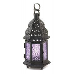Shades of violet lavender and purple will dance across your tabletop when you light a candle inside this exotic metal candle lantern. It features a black frame with intricate cutouts and six purple glass panels that turn candlelight into dazzling glow. Candle not included. Purple Moroccan Style Lantern by Rustica House. #myRustica
