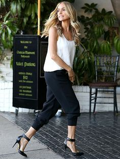 Kristin Cavallari in black pants, flowy white sleeveless shirt, and black Chinese Laundry heels with ankle straps.