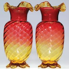 Twin Amberina mantle vases their bodies internally ribbed and swirled. The vessels have amber flirtatious ruffles encircling the rims and are elevated on tooled scalloped baseswit floral motifs.