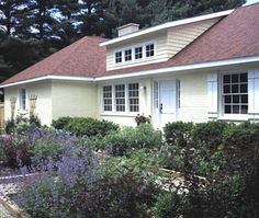 The remodel involved increasing the pitched roofline, adding a dormer to shed light into the living room, invigorating the exterior by painting red bricks yellow, installing new windows, and creating a colorful garden leading to the front door.