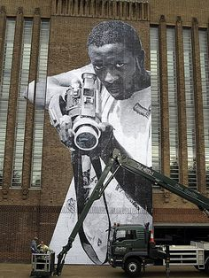 Street Artist JR proving a camera can be just as menacing as a gun...