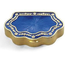 A two-colour gold and enamel snuff box, Hahn, workmaster Carl Blank, St Petersburg, late 19th century of cartouche form, the lid later enamelled in translucent royal blue over wavy sunburst engine-turning, the chased double laurel border enclosing flowerheads and leaf sprays, reeded sides and base, 56 standard, further struck with Polish control marks
