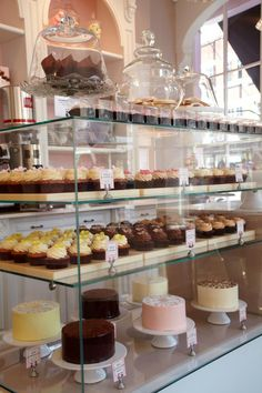 by Peggy Porschen Cakes. simple clear plastic boxes for one cupcake. Large glass domes for others. Light filled design where the emphasis is on products