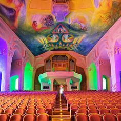 "This is the big auditorium of the Goetheanum. The ""Grosser Saal"" is used by the anthroposophical movement for acting and eurythmy. The paintings shall show the human development.  The beautiful colors at the end of the hall come from the stained glass.  Design of the Goetheanum and the paintings by Rudolf Steiner, built 1924-1928."