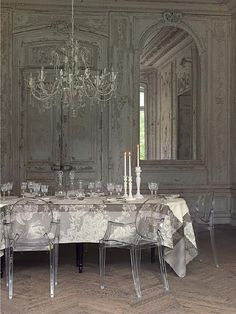 Glass chandy and chairs, transparent lace and light grey walls, all make for a not only elegant, but ethereal dining experience... so beautiful!
