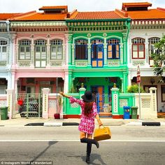 Self-timer pro: Saward, pictured in Singapore, has perfected using a tripod to take pictures when she's alone, using a self-timer function and running into the frame of the photo