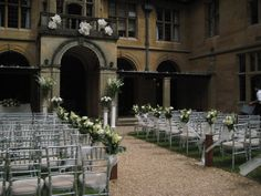 An outside ceremony at Coombe Lodge with decorated chairs, pedestals and balcony