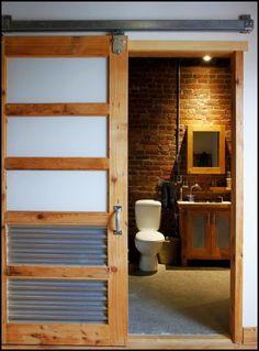 Sliding Barn Door on a Bathroom with a Brick Wall.