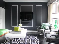 Charcoal-colored walls and black hardwood floors make a dramatic statement in this Art deco living room. White accents stand out in stark contrast. A graphic black and white rug defines the seating area, and a pair of modern metal chairs offer seating for conversation or TV viewing.