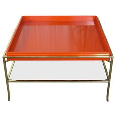Cocktail Table | Orange | Tommi Parzinger |USA 1960's  Removable square lacquered tray rests in the brass structure. Table has lower glass shelf. Brass has been polished and lacquered. The wood tray has been refinished in a rich, red-orange lacquer.