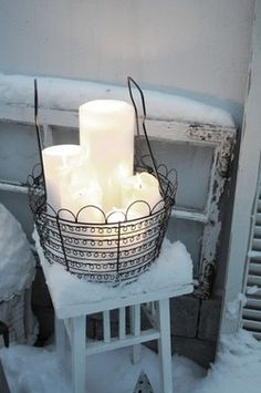 Winter white candles in a black wire basket surrounded by snow. #partylite #candles #decoration #winter #talvi #vinter