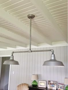 Living and Dining Room Renovation Reveal- My dad created a custom light fixture for our dining room using outdoor barn lights, galvanized pipe, and plumbing fixtures.