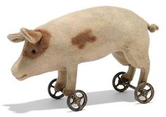 A STEIFF FELT PIG ON WHEELS, (1114), pink with brown spots, black boot button eyes, inoperative squeaker, gold-painted cast metal four-spoke wheels and FF button, circa 1908 --8½in. (21.5cm.) long (discoloured, slight water mark)