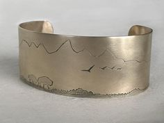 Roaming Buff on the Range Cuff, Daphne Lorna jewelry. Buffalo roaming with mountains. Just over an inch wide cuff. Antique Matte Brass finish or a Matte Silver finish. Silver Cuff, Silver Earrings, Sterling Silver, Copper Gifts, Silver Jewelry Cleaner, Feather Pattern, Antique Brass, Cuff Bracelets, Unique Jewelry