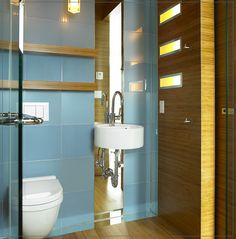 The lights in the cabinet door and large (back-painted glass?) tiles make this washroom really shine!