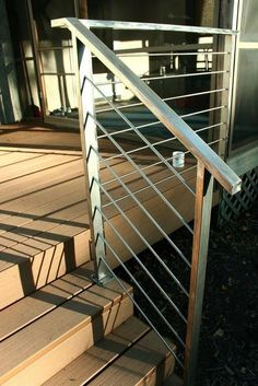 Simple, stainless steel deck rails add a modern touch to outdoor decor. Stainless Steel Stair Railing, Steel Handrail, Steel Stairs, Outdoor Stair Railing, Deck Railings, Porch Handrails, Metal Railings, Cable Railing, Staircase Railings