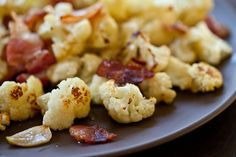 Preheat oven to 375F. On a baking sheet, toss together the cauliflower, garlic slices, bacon and olive oil. Roast for 20-25 minutes until bacon is crisp and cauliflower is cooked through. Season with the roasted cauliflower with salt and pepper to taste.