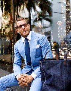Consider pairing a light blue suit with a white oxford shirt for a sharp classy look.   Shop this look on Lookastic: https://lookastic.com/men/looks/suit-dress-shirt-tote-bag-tie-pocket-square/10655   — White Dress Shirt  — Navy Tie  — White Pocket Square  — Navy Denim Tote Bag  — Light Blue Suit