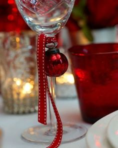 small ornaments and ribbon on each wine glass: christmas table details <3 christmas decoration ideas, christmas ideas. ornament garland, christmas parties,  hannukah, new years, christmas table