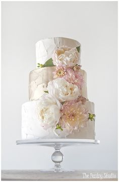 This gorgeous wedding cake features metallic gold and ivory  buttercream and soft fresh floral. Cake design made by The Pastry Studio located in Daytona Beach, Florida.