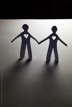 Two paper figures hold hands with hearts on their chest.
