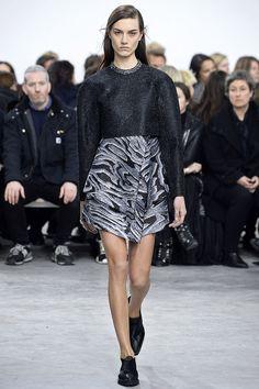 Proenza Schouler, New York Fashion Week Fall 2014. Black metallic long-sleeved top, wrapped black and grey skirt in a wood grain resembling pattern, black flats.