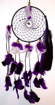 Black genuine suede wrapped around a 9-inch metal ring. The purple c-lon webbing is accentuated with Black and White Agate, Amethyst, and brass beads with the Baltimore Ravens Logo in the center. The dreamcatcher is finished off with black tassels adorned with purple, black and white turkey t-feathers, and black and purple turkey feathers hanging from the side. Black Agate is used for calming and soothing anxiety. White Agate is used to promote general protection and tranquility. Amethyst…
