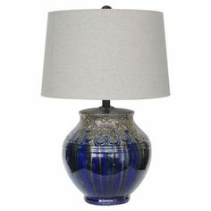 "Ceramic table lamp with textured scrolling details and a metallic silver reactive glaze finish.     Product: Table lampConstruction Material: Ceramic and fabricColor: Metallic silver and blueFeatures:  3-Way switchMatching finial Accommodates: (1) 150 Watt bulb - not includedDimensions: 25"" H x 16.5"" Diameter"
