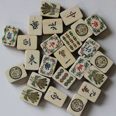 Sampling of Japanese domestic bone and bamboo mahjong tiles. The set is missing the summer and orchid tiles. The one dot is a dragon chasing a fire pearl. Set is most likely from the 1930s. The flower tiles have brighter paint since they were not used for play. Mah Jongg.