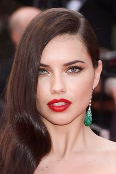 #AdrianaLima - Red lipstick and winged black liner with side swept curls.