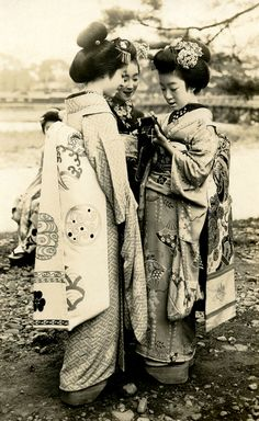 Maiko Hatsuko holding a camera, while two other Maiko girls (Apprentice Geisha) look on, a postcard from the mid 1920s.