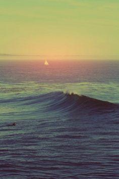 Beautiful surfer, wave and sailboat