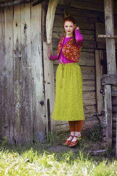 """Die rote Öko-Baumwollweste """"Hedvig"""" ist mit dem fuchsiafarbenen Langarmshirt """"Svalört"""" und dem kräutergrünen Baumwollrock """"Hanna"""", der einen elastischen Bund hat, kombiniert."""
