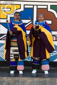 Photograph of Ndebele women in tribal dress outside a traditionally painted house, South Africa - License this photo from Steve Bloom Images
