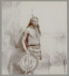 Portrait of Tonka-Wicakin (Takes Enemy) with face and body paint and holding painted shield, Sioux, 19 AUG 1901