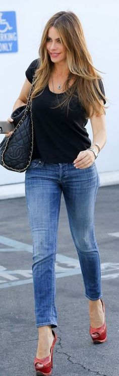 Blue jeans, black chain handbag, and red snake platform pumps