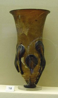 Glass claw beaker, dark brown with flaring rim, thin self-coloured trailed spiral; two rows of claws. Fragmentary condition.