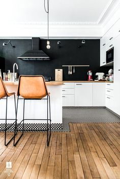 A black-and-white kitchen with leather bar stools, black backsplash, butcher block counters and black and white printed penny tiles. Love!