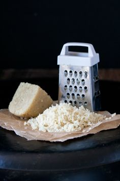 Pile of grated vegan parmesan cheese in front of a grater