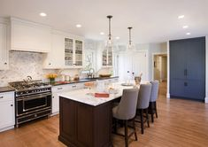 Gorgeous kitchen with large glass bell jar pendants over chocolate brown kitchen island accented with beadboard trim  and Bianco Statuario Marble countertops lined with Restoration Hardware 1940s French Upholstered Barrelback Counter Stools.