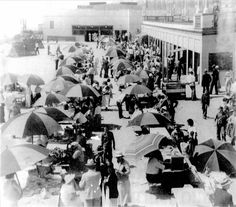 Umbrella rentals near Huntington Beach pier, circa 1930s.  The Saltwater Plunge can be seen in the background.  Photo, City of Huntington Beach archives.